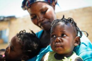 Frau in Afrika mit zwei Kindern. Sie nimmt an einer Selbsthilfegruppe teil