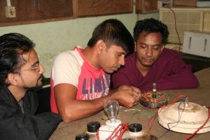 Drei Männer in Bangladesch lernen, elektrische Motoren zu bauen.