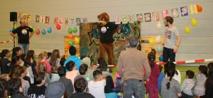 Der Inselbär (Maskottchen der Lichtinsel im Bärenkostüm) steht auf einer Bühne, davor sitzten Kinder