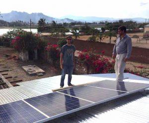 Mitarbeiter beim installieren von Solarpanelen auf einem Dach, was auch das Projekt nachhaltige Landwirtschaft fördert.
