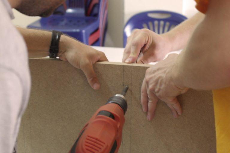 Innovative Entwicklungshilfe durch Möbelproduktion - auf dem Bild wird gerade ein Regal zusammengeschraubt.